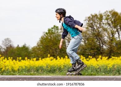 Teenage girl rollerblading against blue sky