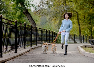 A teenage girl running on the street with two welsh corgi pembroke dogs