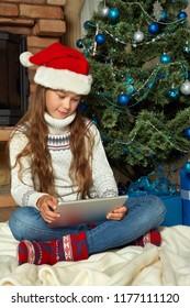 teenage girl in Santa hat with tablet computer near Christmas tree. xmas kid