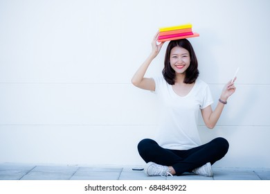 Teenage girl sat smiling happily. On a white background, she placed a book on her head and her hands were pointing up.