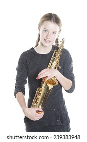 teenage girl with saxophone against white background in studio