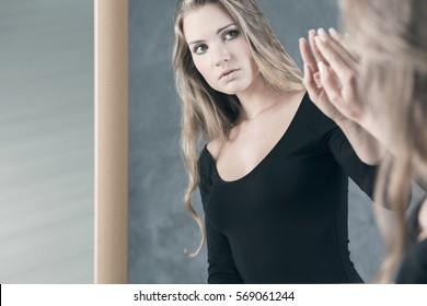 Teenage girl with schizophrenia afraid of her mirror reflection