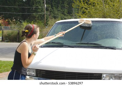 Teenage girl scrubs van windshield