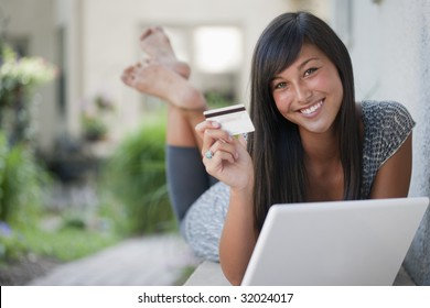 Teenage girl shopping on line with credit card and laptop