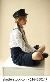 A teenage girl sits in full view. Cap, shorts and fashionable boots.