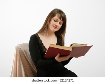 Teenage girl sits on chair and holds the large open textbook. Her look is focused on pages of book. She is wearing black dress with low neckline. She's got long dark hair.