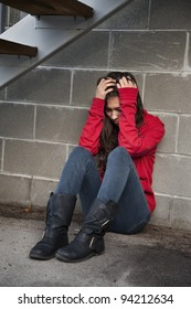 Teenage girl sitting against brick wall in a depressed state.