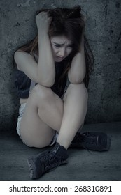Teenage girl sitting alone and looks depressed, shot against a dark background