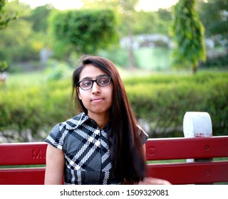 A Teenage girl sitting on banch into public park and enjoying fresh air from nature.
