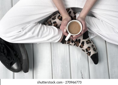 Teenage girl sitting on floor holding a coffee cup. Body part close up on wooden surface