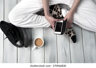 Teenage girl sitting on floor holding her smartphone. Body part close up on wooden surface
