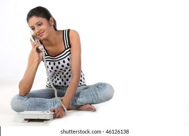 Teenage girl sitting on the floor talking over telephone