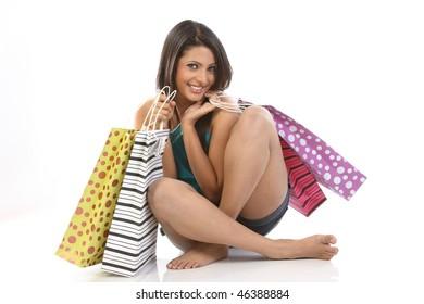Teenage girl sitting on floor with shopping bags