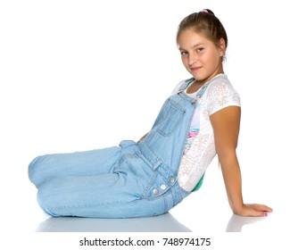 A teenage girl is sitting on the floor. Isolated on white background.
