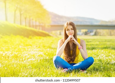 Teenage girl sitting outdoors in park on green grass. Young woman outside in summer relaxing enjoying nature
