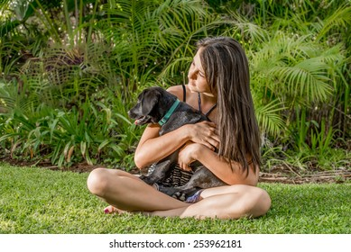 A teenage girl, sitting outside on the lawn, while playing with a Labrador puppy.