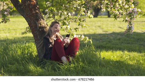 teenage girl sitting under blossoming pink apple tree using smartphone and laughing