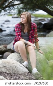 Teenage girl sitting at the water with a worried expression