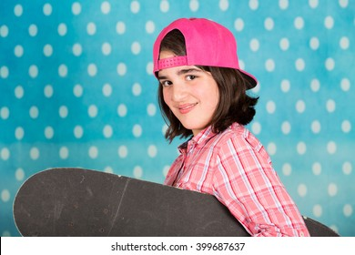 Teenage girl with skateboard with a blue background