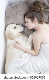 Teenage girl sleeping with her dog next to. Vertical shot with swab light from studio flax.