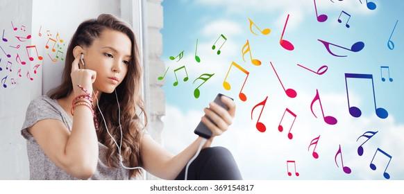 teenage girl with smartphone and earphones