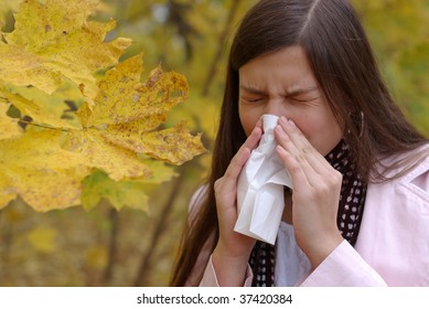 teenage girl sneeze into handkerchief with maple leaf in foreground