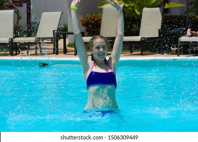 Teenage girl splashing water and playing in luxury hotel swimming pool. Summer vacation concept