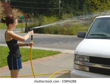 Teenage girl sprays van with a hose