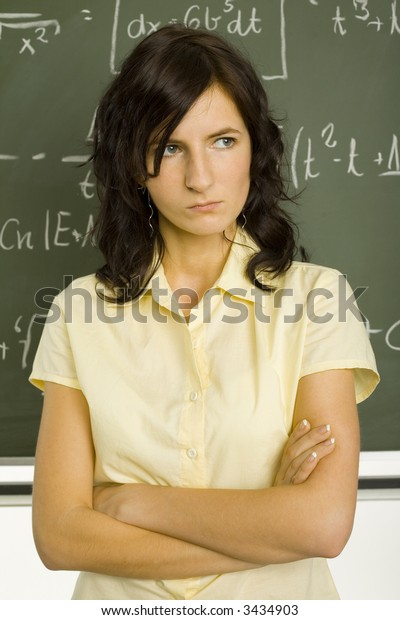 Teenage girl standing in classroom, in front of blackboard with crossed arms. front view