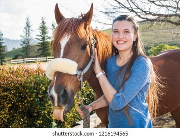 Teenage girl standing with her chestnut Arab horse looking at the camera smiling close up, having fun with the horse sticking out his tongue.