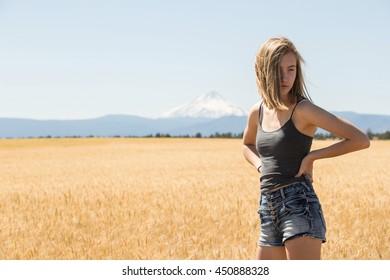 Teenage girl standing in a wheat field