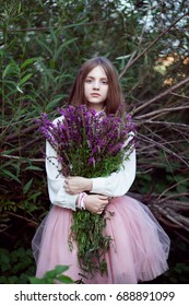 A teenage girl stands near a tree with flowers in her hands