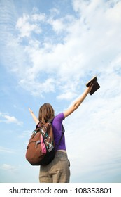 Teenage girl staying with raised hands against blue sky
