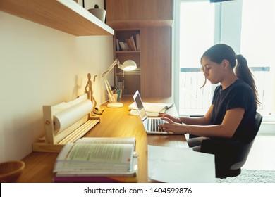Teenage girl studying in her room