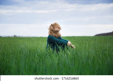 teenage girl in sweater and long emerald-colored skirt sits on ground among field of young grass, her face is covered with hair that flutters in  wind. Harmony, inspiration, relaxation, self-isolation