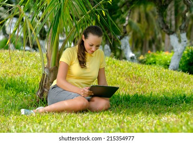 Teenage Girl with tablet outdoors. Young woman using pc outdoor laying on grass. Nature background.