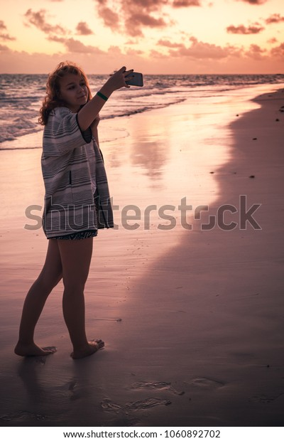 Teenage girl taking selfie photo on the beach in early morning