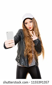 Teenage girl taking a selfie posing, gesturing peace. Closeup studio portrait of young woman photographing herself using smartphone. Isolated on white background.