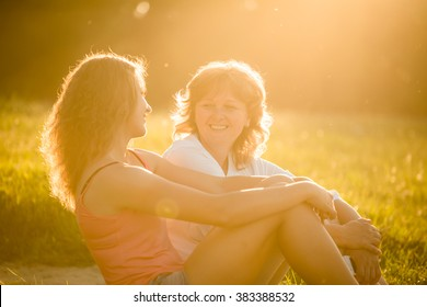 Teenage girl talking with her mother sitting on grass in nature, flare from setting sun in photo