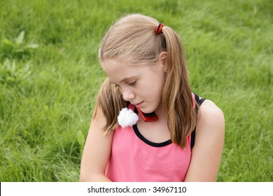 Teenage girl talks on cellural phone on green grass background