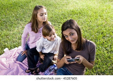 Teenage girl texting on mobile phone while younger siblings watch