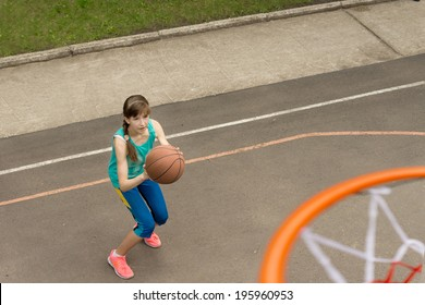 Teenage girl throwing a basketball at the net bending her knees as she prepares to launch herself into the air
