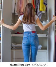 Teenage girl tidying up the wardrobe at home. Everything is folded neatly. Everything is in its place. Concept of tidy Interior and collaboration of young people in the housework