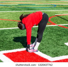 A teenage girl track and field runner is stretching her hamstrings during winter outdoor practice wearing a red sweatshirt and black spandex.