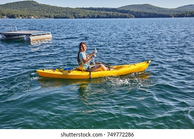 Teenage girl trying out a kayak on a sunny day at Merrymeeting Lake
