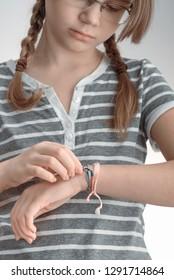 Teenage girl tying handmade baubles on her hand.