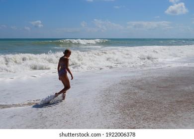 teenage girl walking alone along the empty seashore on the sunny day.