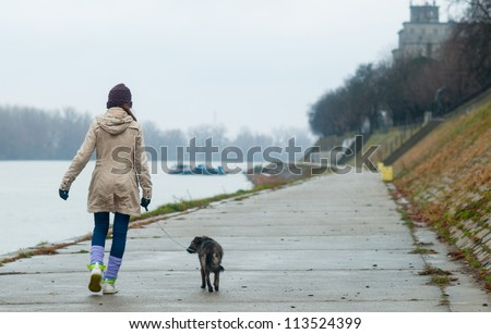 Teenage girl walking the dog on cloudy autumn day.