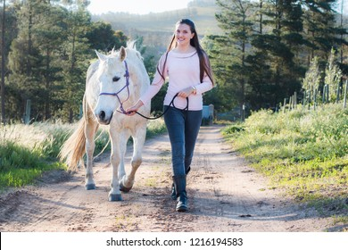 Teenage girl walking next to a white Boerperd horse on a dirt road, leading him with his head collar looking at the camera smiling.