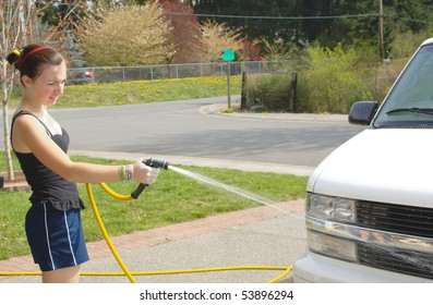 Teenage girl washes van with hose